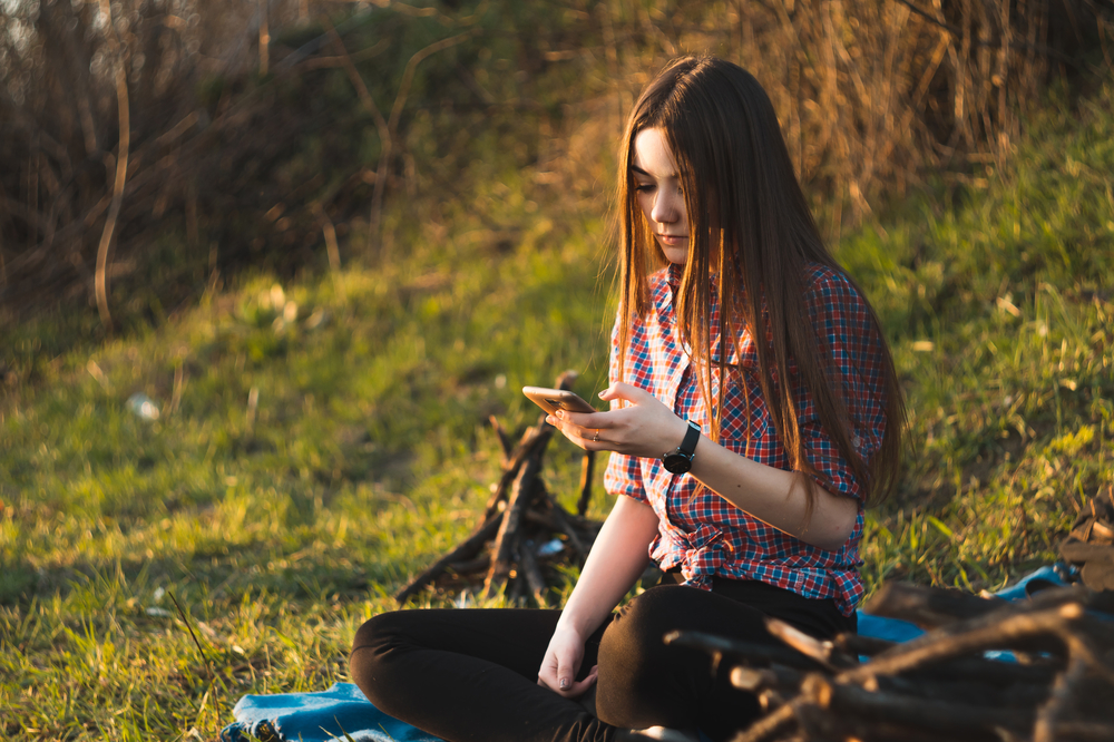 Young beautiful girl sitting by the fire at a picnic in the summ